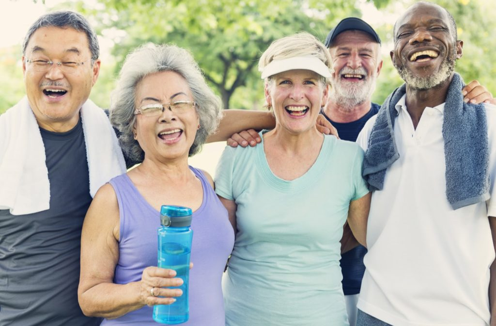 Happy seniors gathering together after exercising together outside
